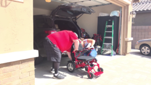Dave and his wife working together to get his chair into his car.